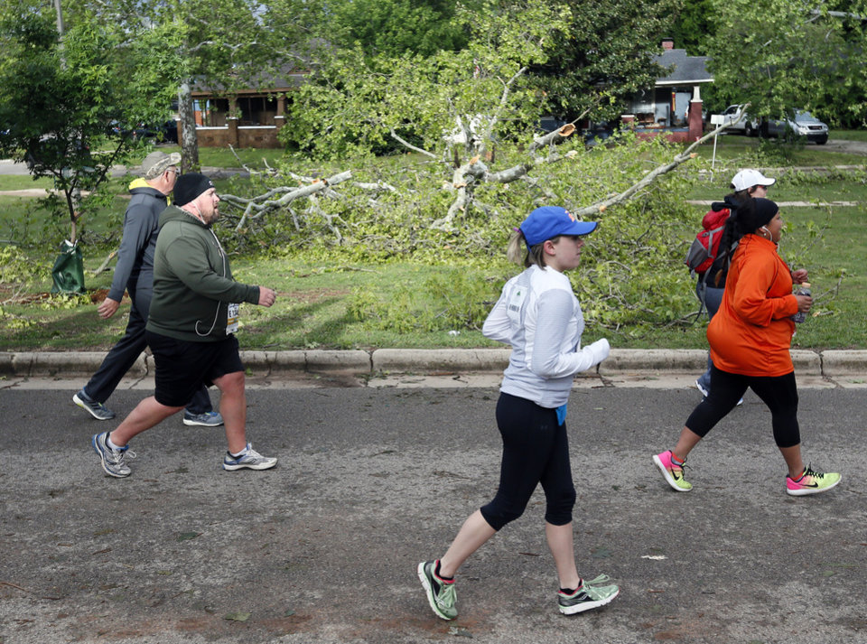 Photo - Runners pass fallen trees from the previous day's thunderstorms at NW 28 and Harvey Parkway during the Oklahoma City Memorial Marathon in Oklahoma City, Sunday, April 30, 2017. Photo by Nate Billings, The Oklahoman