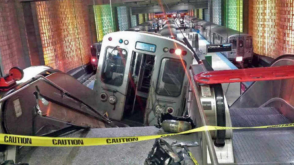Photo - A Chicago Transit Authority train car rests on an escalator at the O'Hare Airport station after it derailed early Monday, March 24, 2014, in Chicago. More than 30 people were injured after the train