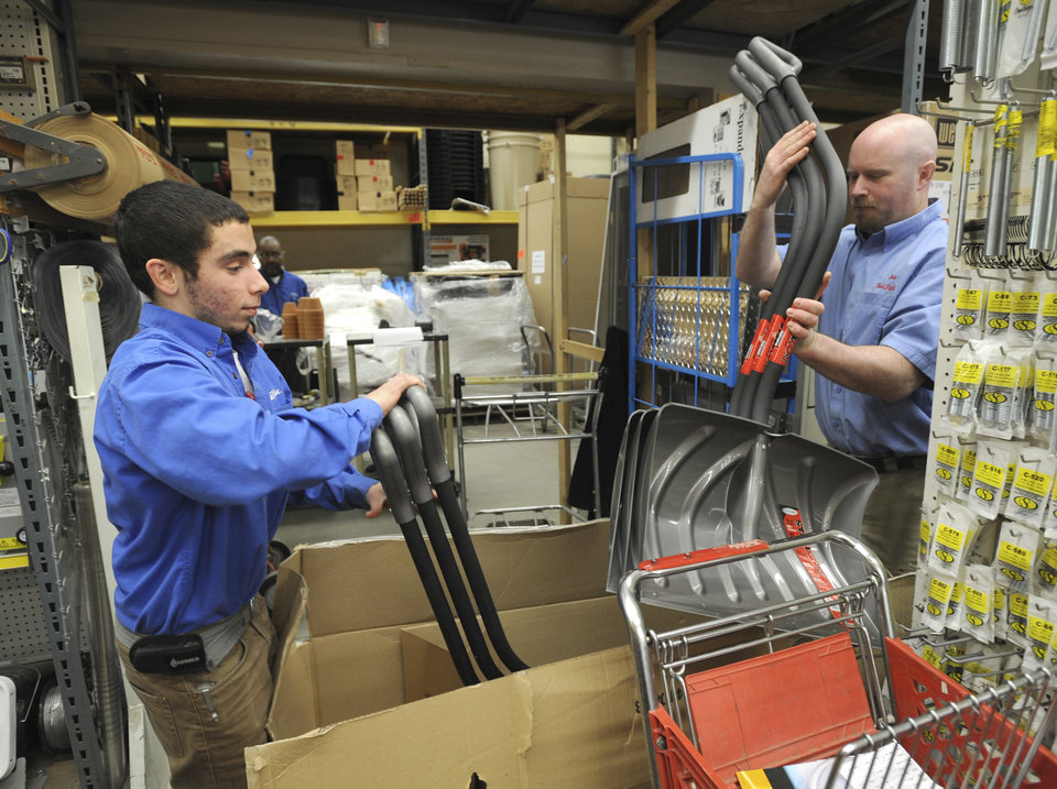Photo - Felipe DaSilva, left, a department manager, and store manager Joe Hogbin, right, un-box more snow shovels to bring to the front of the K&B True Value store in Annapolis, Md., Monday, Marh 4, 2013 The coming possibility of a late winter snow storm has people heading to the store, in Bay Ridge, for supplies like snow shovels, window scrapers and ice melt.  (AP Photo/The Capital Gazette,Paul W. Gillespie)