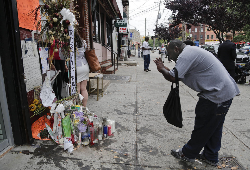 Photo - A passer-by stops to take a photo of a makeshift memorial for Eric Garner, Friday, Aug. 1, 2014, in the Staten Island borough of New York. Garner died after he was put in a chokehold while being arrested at the site last month for selling untaxed loose cigarettes. On Friday, the medical examiner ruled Garner's death to be a homicide caused by a police chokehold. (AP Photo/Julie Jacobson)