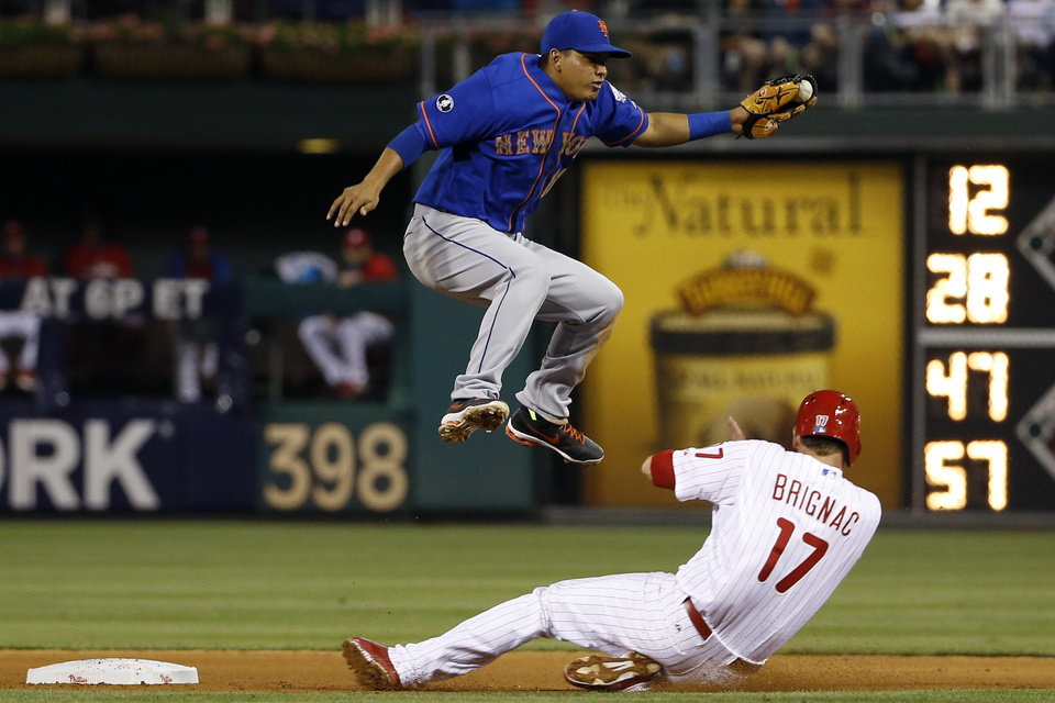 Photo - Philadelphia Phillies' Reid Brignac, right, slides into second base under New York Mets shortstop Ruben Tejada to advance on a ball hit by A.J. Burnett during the fourth inning of a baseball game, Friday, May 30, 2014, in Philadelphia. Burnett reached first base and Brignac was safe at second on the throwing error by catcher Travis d'Arnaud. (AP Photo/Matt Slocum)