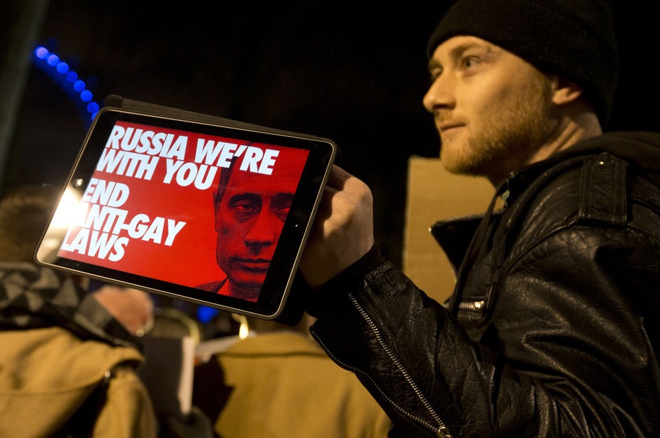 Photo - A Lesbian and Gay Rights activist holds up a tablet with a picture of a placard, during a demonstration aimed to coincide with the upcoming Winter Olympics in Sochi, Russia, against laws aimed at stifling Gay Rights in Russia, opposite Downing Street in London, Wednesday, Feb. 5, 2014. In London, about 150 people rallying outside Prime Minister David Cameron's office in London urged McDonald's and the IOC's other sponsors to speak out. The activists there said they plan to deliver a petition signed by more than 100,000 people to a nearby McDonald's restaurant.  (AP Photo/Alastair Grant)