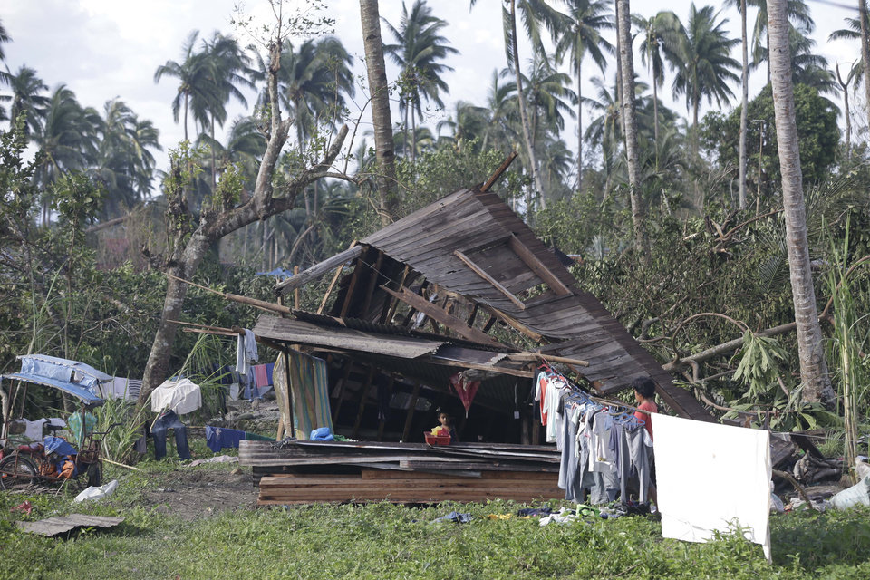 A resident dries their clothes amidst their toppled house at the flash flood-hit village of Andap, New Bataan township, Compostela Valley in southern Philippines Wednesday Dec. 5, 2012. Typhoon Bopha, one of the strongest typhoons to hit the Philippines this year, barreled across the country's south on Tuesday, killing scores of people while triggering landslides, flooding and cutting off power in two entire provinces. (AP Photo/Bullit Marquez)