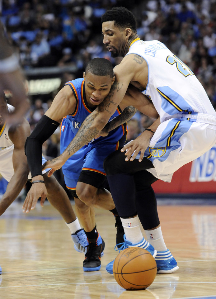 Photo - Oklahoma City Thunder guard Russell Westbrook (0) loses the ball as he runs into Denver Nuggets forward Wilson Chandler (21) during the first half in game 4 of a first-round NBA basketball playoff series Monday, April 25, 2011, in Denver. (AP Photo/Jack Dempsey)