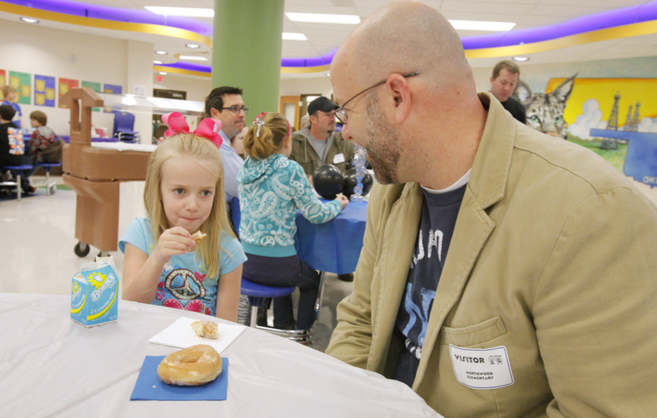 "First-grader Sarah Gilstrap, 7, enjoying a doughnut with her dad John Gilstrap during a ""Donuts with Dad"" breakfast at Northwood Elementary School in Piedmont Tuesday, Jan 24, 2012. Photo by Paul B. Southerland, The Oklahoman"
