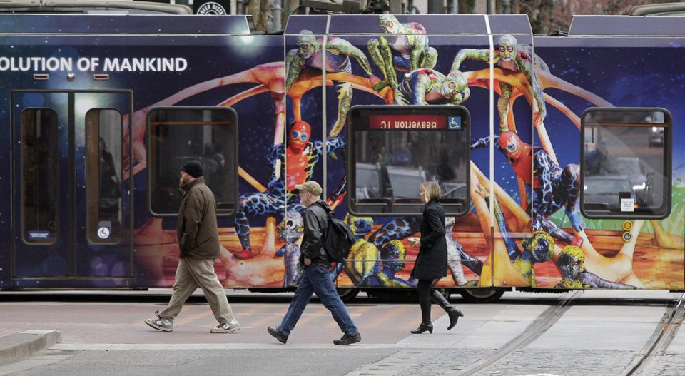 Photo - Pedestrians walk by a colorful MAX train in Portland, Ore., Monday, March 10, 2014.  While use of buses, trains and subways is on the rise in many cities across America, ridership in the Portland area's much touted system has actually fallen off, according to new data released by the American Public Transportation Association. (AP Photo/Don Ryan)