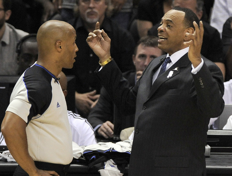 Photo - Memphis Grizzlies head coach Lionel Hollins, right, argues a call with referee Marc Davis during the first half of Game 1 of the Western Conference final NBA basketball playoff series against the San Antonio Spurs, Sunday, May 19, 2013, in San Antonio. (AP Photo/Darren Abate)