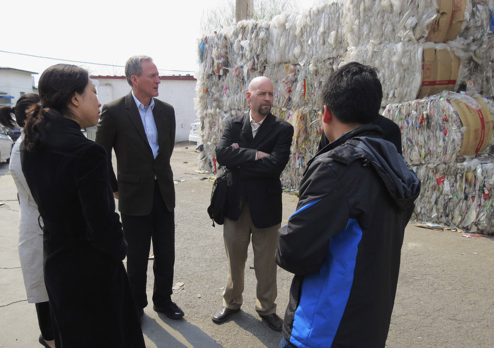 Photo - FILE - In this April 7, 2013 file photo provided by Gov. Dennis Daugaard's office, South Dakota Gov. Dennis Daugaard, center left, and Jake Anderson, right, owner and president of Millennium Recycling in Sioux Falls, speaks with Chinese officials at a recycling center in Beijing. Daugaard will be joined by representatives from 11 companies and groups from around South Dakota when he makes his third trade mission to China May 9-16, 2014. (AP Photo/Gov. Dennis Daugaard's Office, Kelsey Webb, File)