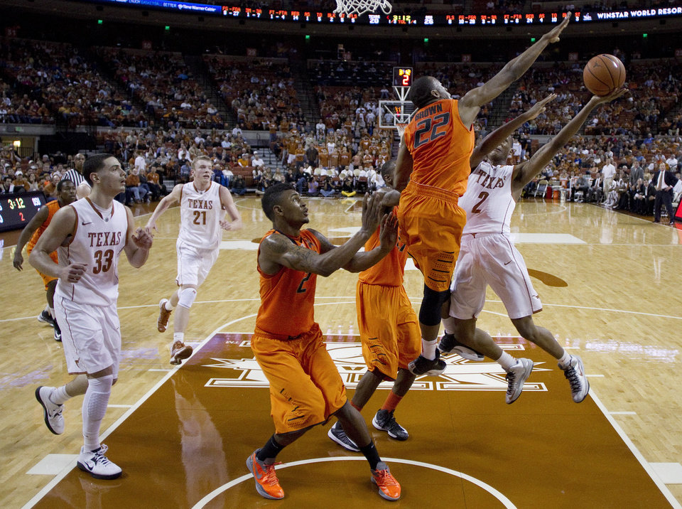 Texas' Demarcus Holland (2) shoots as Oklahoma State's Markel Brown (22), Le'Bryan Nash (2) and Kamari Murphy, center, defend during the first half of an NCAA college basketball game, Saturday, Feb. 9, 2013, in Austin, Texas. (AP Photo/Eric Gay) ORG XMIT: TXEG104