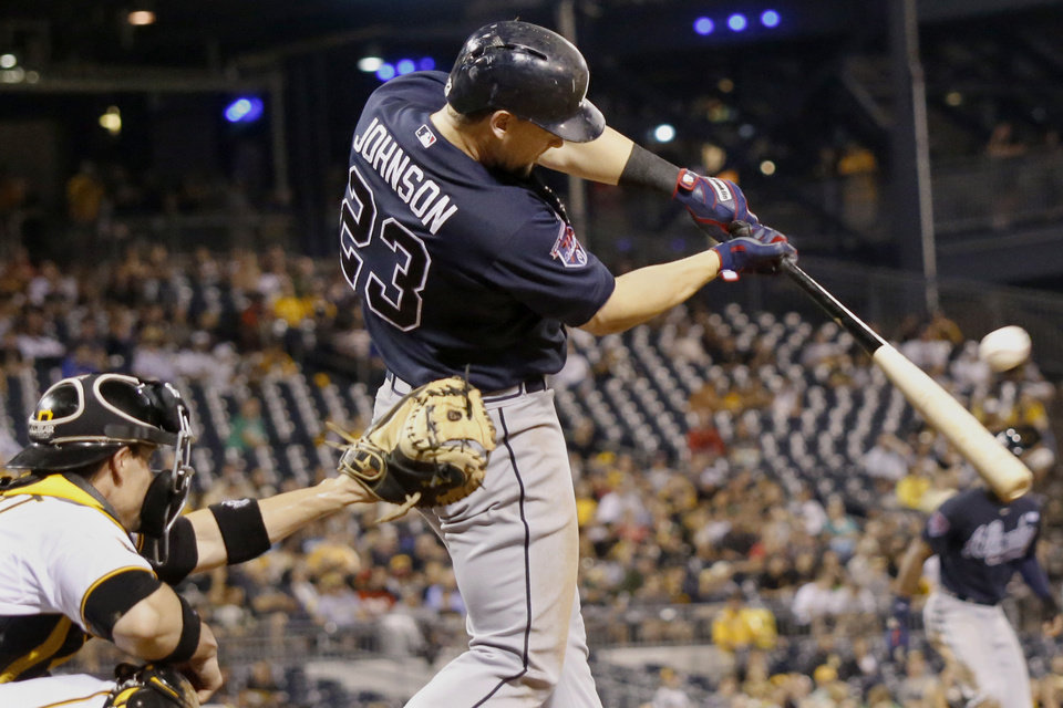 Photo - Atlanta Braves Chris Johnson (23) hits a bases-loaded single to drive in one run in the sixth inning of the baseball game against the Pittsburgh Pirates on Wednesday, Aug. 20, 2014, in Pittsburgh. (AP Photo/Keith Srakocic)