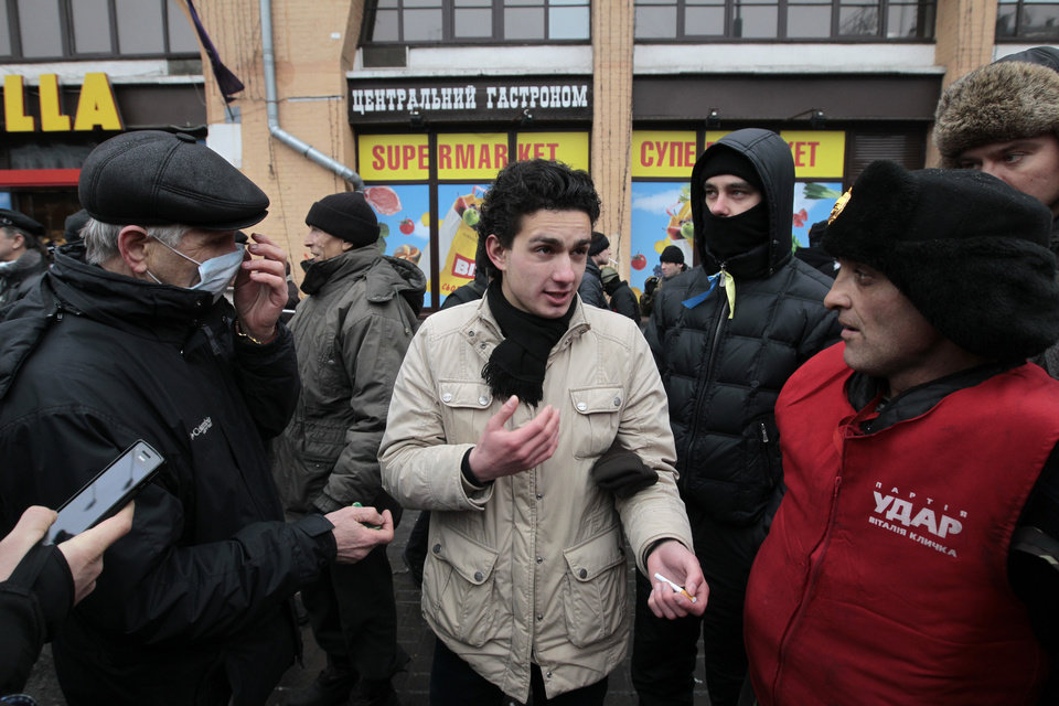 Photo - A man opposed to the anti-government protesters who have held central Kiev for more than two months argues with a protester, who is wearing a vest with the emblem of the party of former boxing champion and protest leader Vitali Klitschko in  Kiev, Ukraine,  Saturday, Feb. 8, 2014. Thousands of people angered by months of anti-government protests in the Ukrainian capital converged on one of the protesters' barricades Saturday, but retreated after meeting sizeable resistance. (AP Photo/Sergei Chuzavkov)