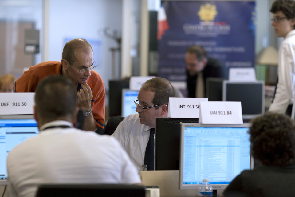 Photo - People work in the French Foreign Affairs ministry's crisis center in Paris Friday, July 25, 2014, after a plane crashed in Mali. At least 116 people were killed in Thursday's disaster, nearly half of whom were French. One of two black boxes was recovered from the wreckage in the Gossi region of Mali near the border with Burkina Faso, and was taken to the northern city of Gao, where a French contingent is based. (AP Photo/Kenzo Tribouillard, Pool)