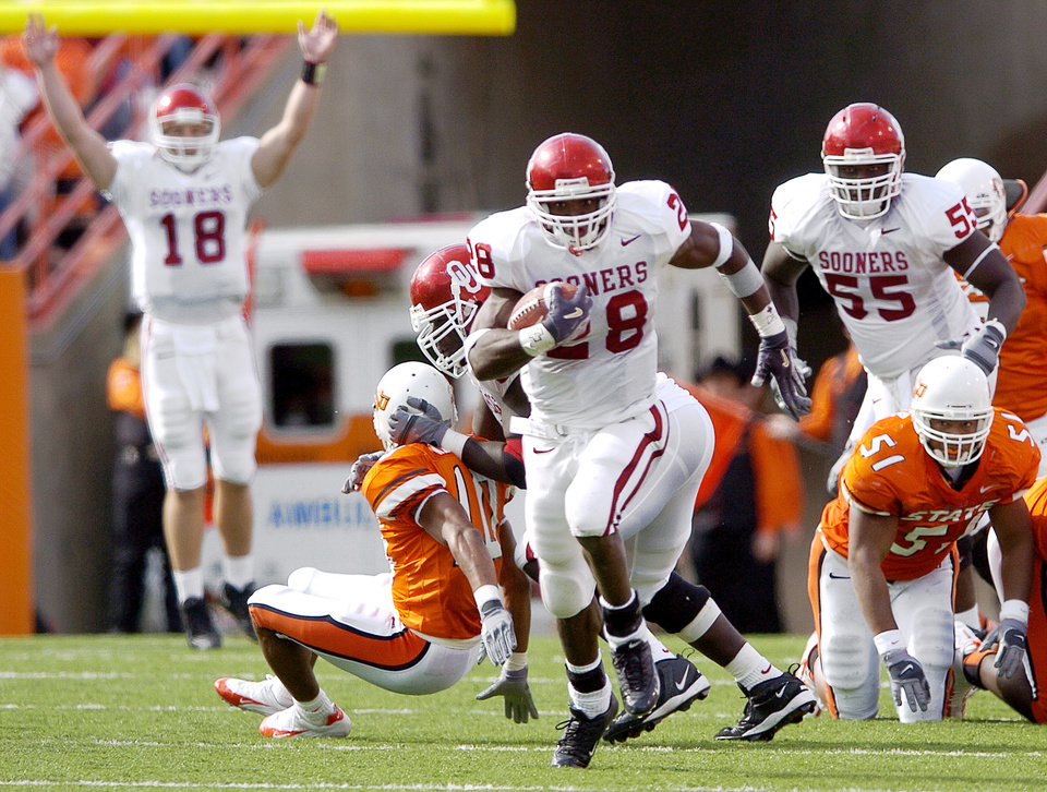 Oklahoma running back Adrian Peterson (28) breaks away from the Oklahoma State defense for an 80-yard touchdown run in the third quarter during the Bedlam college football game between OU and OSU at Boone Pickens Stadium in Stillwater, Okla., October 30, 2004.  At left in the background is OU quarterback Jason White signaling the score as Peterson runs for the goal line. By Nate Billings/The Oklahoman