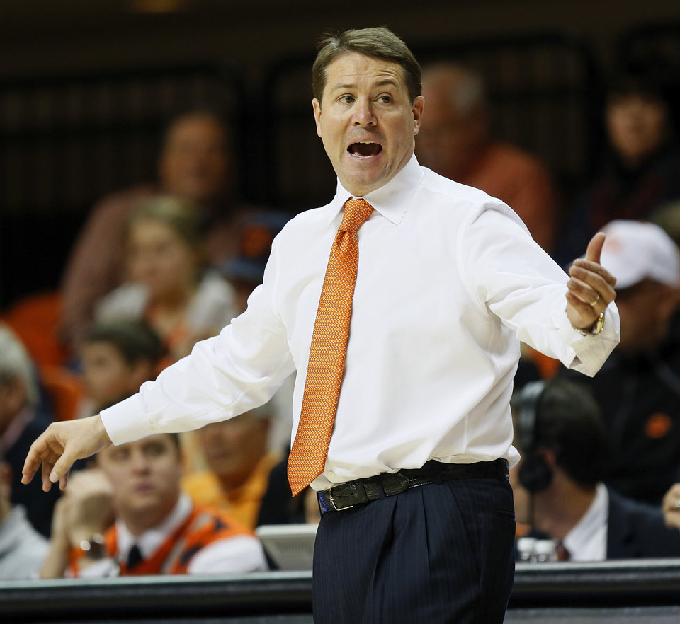 Photo - OSU head coach Travis Ford gives instructions to his players during an NCAA men's basketball game between Oklahoma State University (OSU) and West Virginia at Gallagher-Iba Arena in Stillwater, Okla., Saturday, Jan. 26, 2013. Oklahoma State won, 80-66. Photo by Nate Billings, The Oklahoman