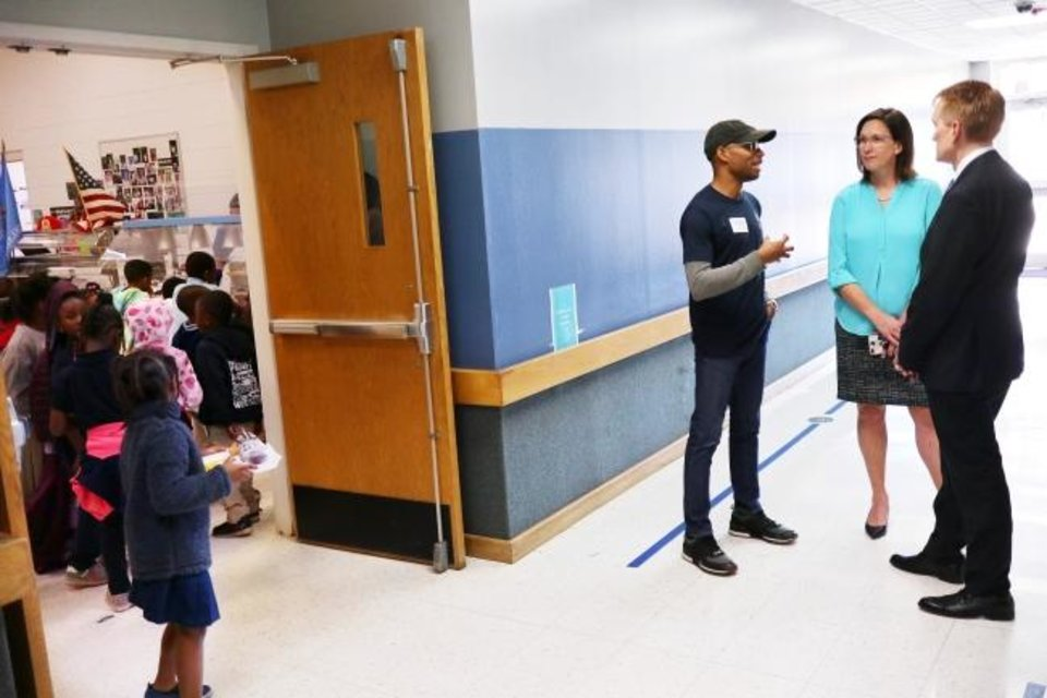Photo -  Ernest Odunze, Principal Michelle Lewis and Sen. James Lankford stop to talk outside the cafeteria during a tour Tuesday of Thelma R. Parks Elementary School to see Restore OKC volunteer work.  [Doug Hoke/The Oklahoman]