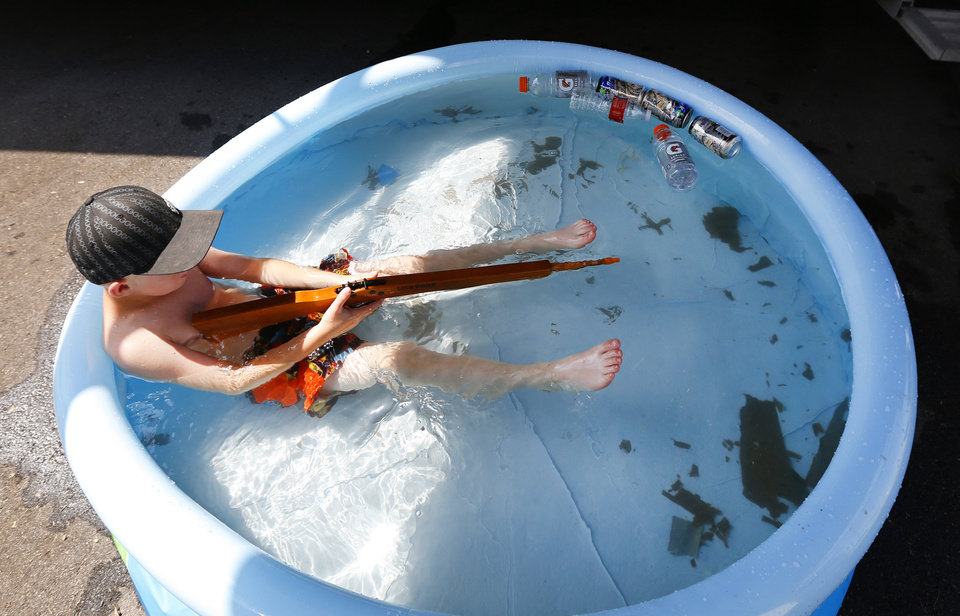 Cactus Barnes, 6, plays in a swimming pool during the International Finals Youth Rodeo at the Heart of Oklahoma Expo Center in Shawnee, Monday July 8, 2013. Cactus is from Maybell, Colorado and his family set the pool up next to their horse trailer. Photo By Steve Gooch, The Oklahoman