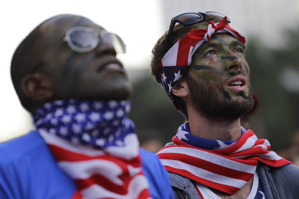 Photo - United States soccer fans with camouflage on thier faces watch the World Cup round of 16 match between Belgium and United States inside the FIFA Fan Fest area during the 2014 soccer World Cup in Sao Paulo, Brazil, Tuesday, July 1, 2014. Belgium beat the United States 2-1 in extra time to reach World Cup quarterfinals. (AP Photo/Nelson Antoine)