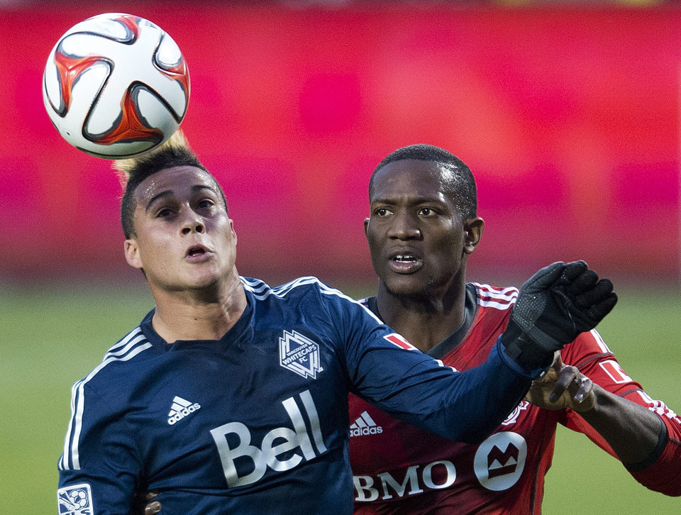Photo - Toronto FC defender Doneil Henry, right, battles for the ball against Vancouver Whitecaps forward Erik Hurtado, left, during first half semi-final Amway Canadian Championship soccer action in Toronto on Wednesday, May 7, 2014. (AP Photo/The Canadian Press, Nathan Denette)