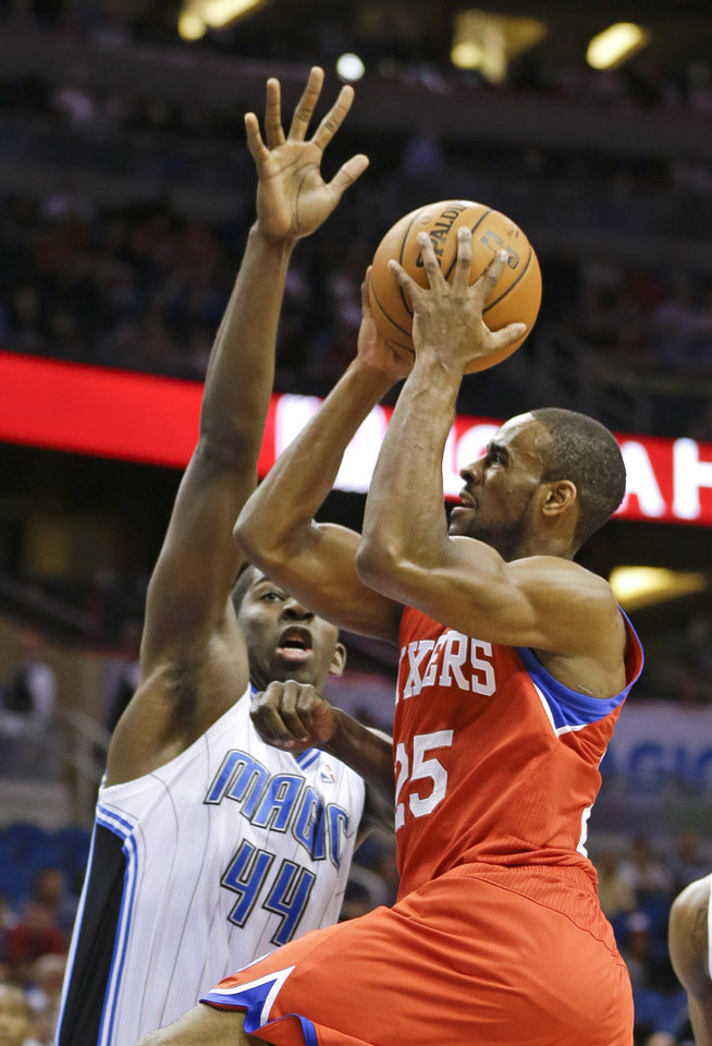Photo - Philadelphia 76ers' Elliot Williams (25) shoots over Orlando Magic's Andrew Nicholson (44) during the first half of an NBA basketball game in Orlando, Fla., Sunday, March 2, 2014. (AP Photo/John Raoux)