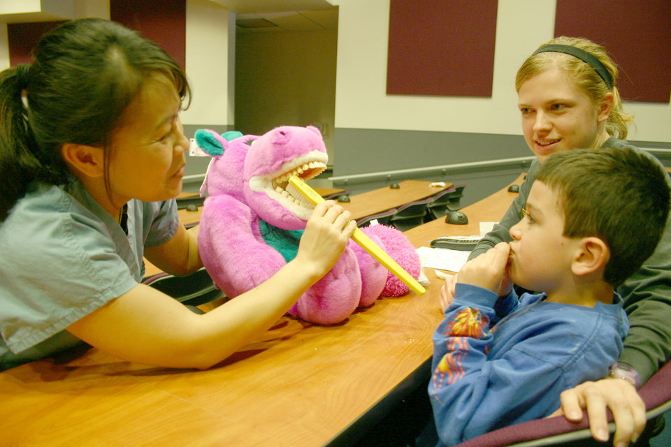 Meta Zimmer, senior dental hygienist student at the University of Oklahoma Health Sciences Center College of Dentistry, uses Sara the toothy, pink hippo to demonstrate proper brushing techniques to McCarty Center patient Zen Deerleader and McCarty Center direct care specialist Laura Hurley. Zimmer was at the McCarty Center teaching dental hygiene methods to the staff and patients as a part of her senior community outreach project. Community Photo By: Greg Gaston Submitted By: Greg,