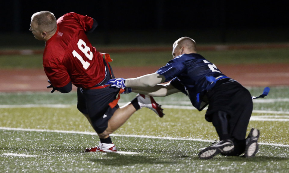 Fireman quarterback Chris Atteberry is sacked by policeman Chad Vincent during the Guns and Hoses charity football game to benefit Compassionate Pointe on Tuesday, Oct. 30, 2012 in Norman, Okla. Photo by Steve Sisney, The Oklahoman