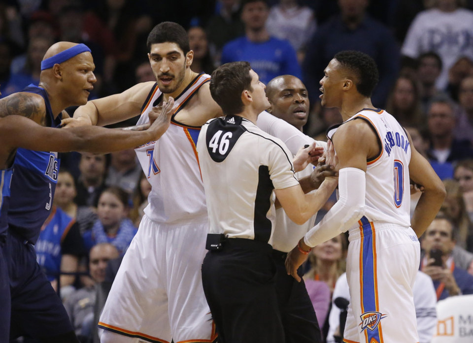 Photo - Officials Ben Taylor (46) and Courtney Kirkland, second from right, separate Dallas Mavericks forward Charlie Villanueva, left, and Oklahoma City Thunder guard Russell Westbrook (0), with help from Thunder center Enes Kanter, second from left, during an altercation in the second quarter of an NBA basketball game in Oklahoma City, Wednesday, Jan. 13, 2016. (AP Photo/Sue Ogrocki)