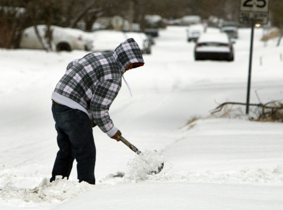 A homeowner uses a shovel to remove snow from his driveway in north Oklahoma City, OK, Friday, December 6, 2013,  Photo by Paul Hellstern, The Oklahoman