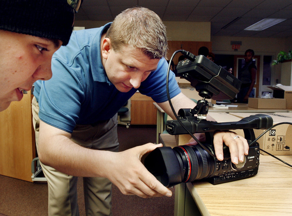 Instructor Chris Kalinski places a lens hood on a camera during class. A new digital video program was launched at Moore Norman Technology Center. Students prepare for a