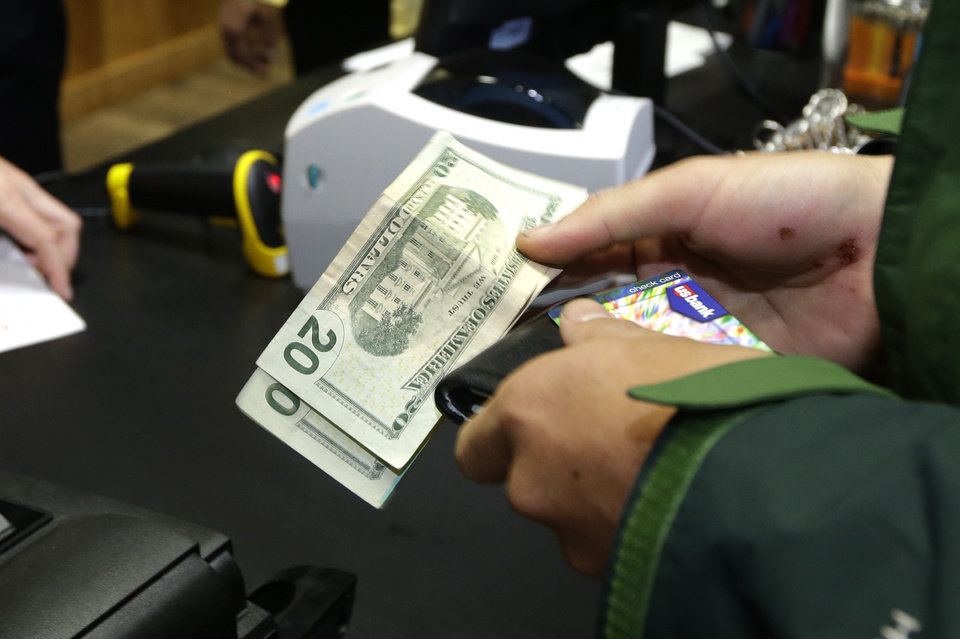 Photo - A customer pays for his recreational marijuana purchase at Top Shelf Cannabis, Tuesday, July 8, 2014, in Bellingham, Wash., on the first day of legal sales in the state.  (AP Photo/Ted S. Warren)