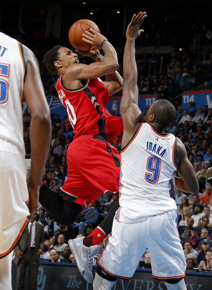 Photo - Oklahoma City's Serge Ibaka (9) fouls Toronto's DeMar DeRozan (10) as he shoots during an NBA basketball game between the Oklahoma City Thunder and the Toronto Raptors at Chesapeake Energy Arena on Wednesday, Nov. 4, 2015. The Thunder lost 103-98. Photo by Bryan Terry, The Oklahoman
