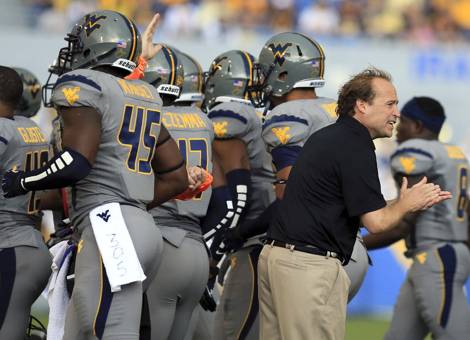 West Virginia coach Dana Holgorsen, right, encourages his players during their NCAA college football game against Maryland in Morgantown, W.Va., Saturday, Sept. 22, 2012. WVU won 31-21 (AP Photo/Christopher Jackson) ORG XMIT: WVCJ124