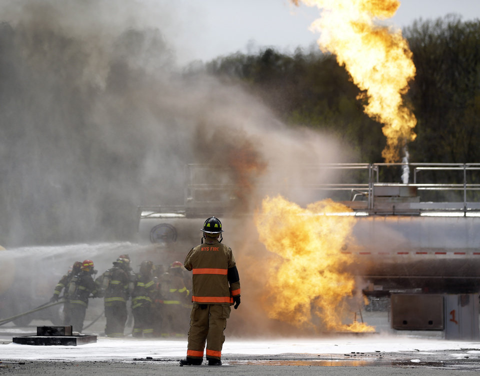 Photo - A State Fire instructor watches as firefighters spray fire suppressant foam to douse flames on a tanker truck in a simulated oil-spill fire during a drill on Wednesday, May 7, 2014, in Albany, N.Y. Firefighters are getting some practice battling crude oil fires as part of stepped-up efforts by the Cuomo administration to address safety threats from increased rail shipment of highly flammable crude from North Dakota to East Coast refineries. The Port of Albany has become a major hub for crude oil transport, with oil trains arriving daily on routes that cross the state from the west and north. (AP Photo/Mike Groll)
