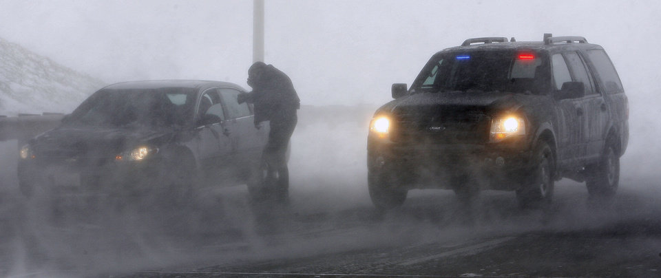 Photo - An El Reno police officer checks on a motorist stranded by a snow storm while parked on SH 81 at I-40 in El Reno Thursday, Dec. 24, 2009. I-40 is closed due to blizzard conditions. Photo by Paul B. Southerland, The Oklahoman