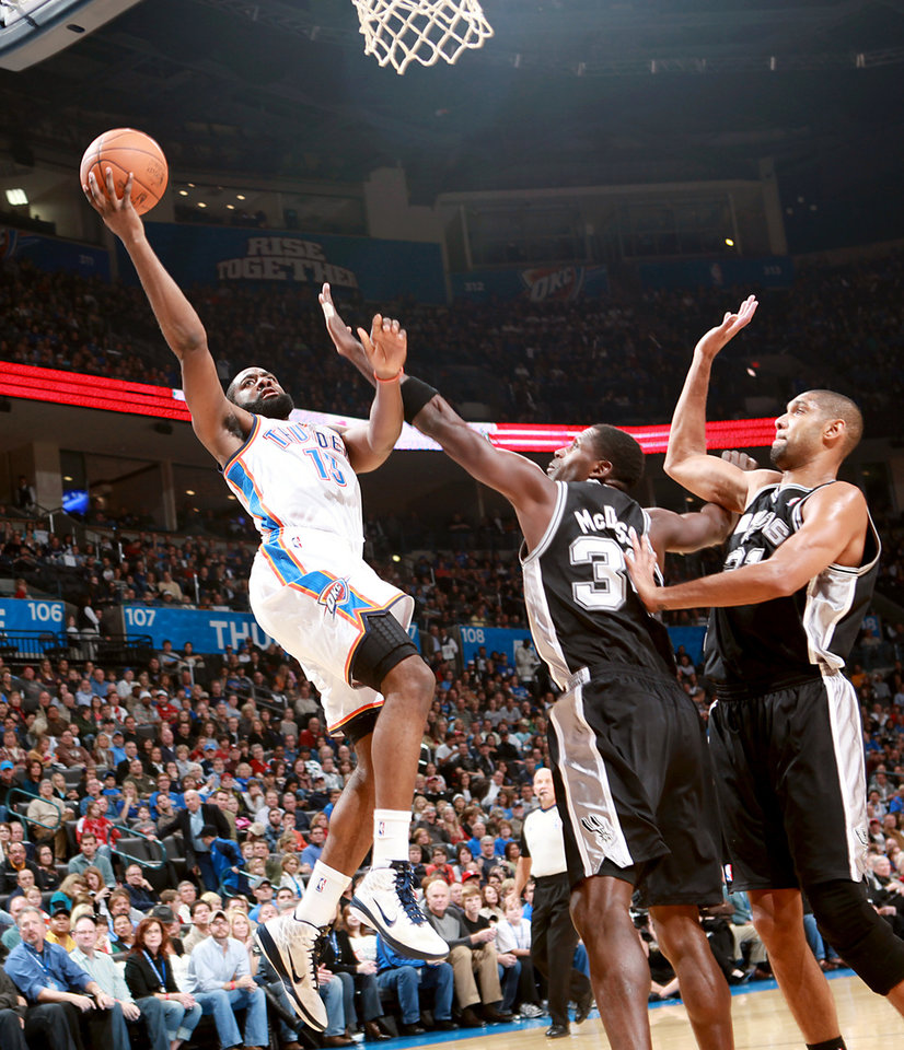Photo - Oklahoma City's James Harden puts up a shot in front of  San Antonio's Antonio McDyess and Tim Duncan during their NBA basketball game in downtown Oklahoma City  on Sunday, Nov. 14, 2010. The Thunder lost to the Spurs 117-104. Photo by John Clanton, The Oklahoman