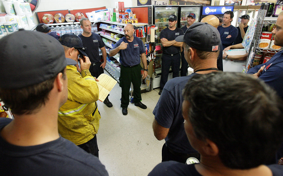 Photo - Escondido Fire Battalion Chief Mike Bertrand, center, thanks all the firefighters in his strike team inside the Lake Hemet Market on Sunday, July 21, 2013. Fire officials started releasing some of the firefighters as the rain helped stop the Mountain Fire. Thousands of people were allowed to return to their homes in Southern California mountain communities near Palm Springs on Sunday, after firefighters aided by heavy rain made substantial progress against a week-old wildfire that has burned across 42 square miles and destroyed seven homes.  (AP Photo/The Press-Enterprise, Terry Pierson)