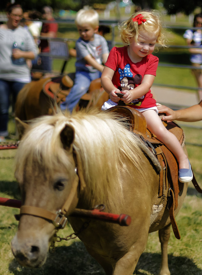 Photo - Charli Stout gets to ride a pony while enjoying the activities during the Yukon Freedom Fest at the Yukon City Park on Thursday , July 4, 2013, in Yukon, Okla. Photo by Chris Landsberger, The Oklahoman