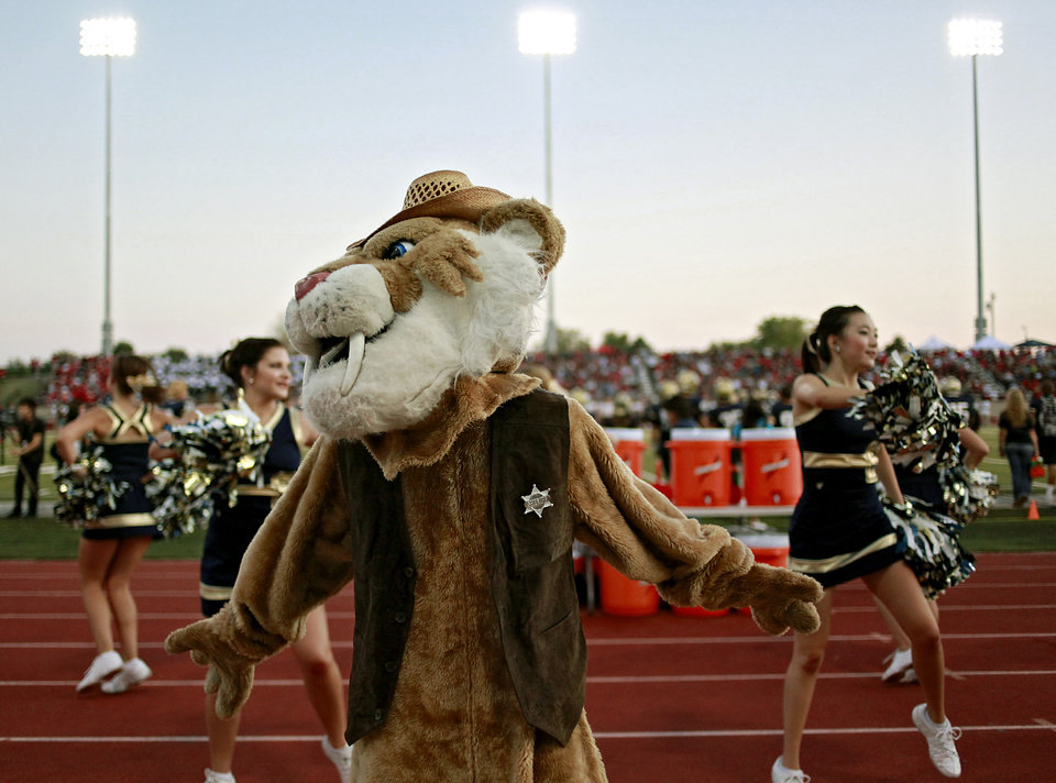 Photo - Southmoore's mascot, Samee the Sabercat, played by Southmoore student Logan Hackworth, dances with the high school cheerleaders during their high school football game at Moore Stadium in Moore, Oklahoma on Friday, September 9, 2011. Photo by John Clanton, The Oklahoman