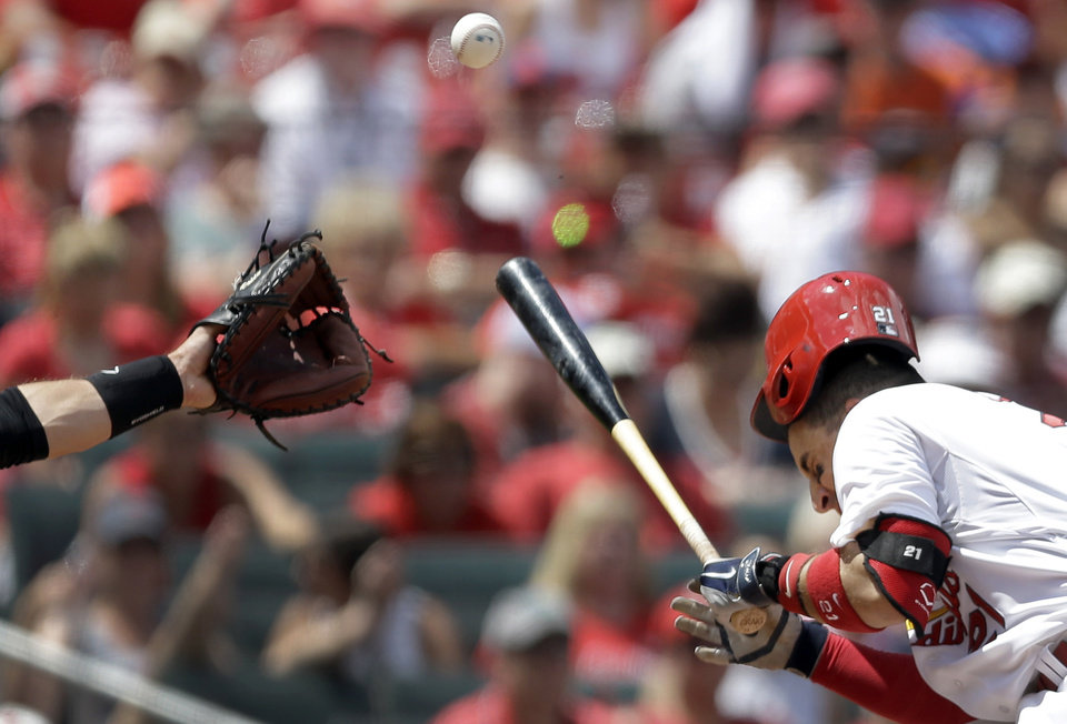 Photo - St. Louis Cardinals' Allen Craig recoils after being hit in the head by a pitch during the third inning of a baseball game against the San Francisco Giants, Sunday, June 1, 2014, in St. Louis. Craig was able to stay in the game. (AP Photo/Jeff Roberson)