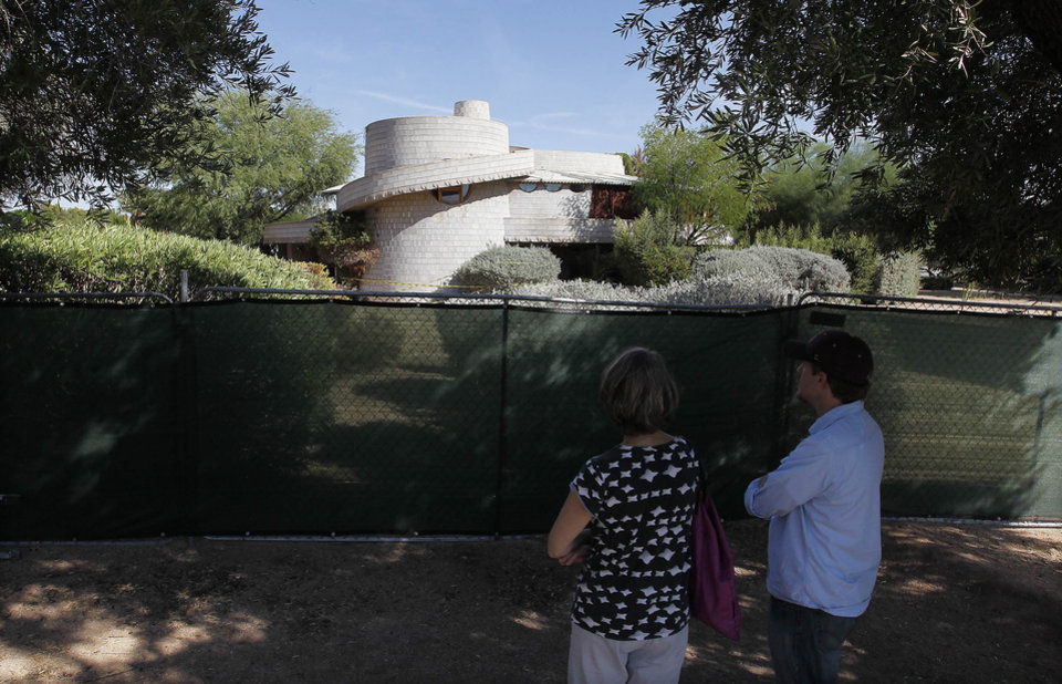 Concerned citizens take a look at a 1952 Frank Lloyd Wright-designed home in the Arcadia neighborhood of Phoenix, Wednesday, Oct. 3, 2012. The city of Phoenix and a developer who was poised to demolish the home have reached an agreement that will put any work on hold while a search continues for a buyer, a city official confirmed Wednesday. (AP Photo/Ross D. Franklin)