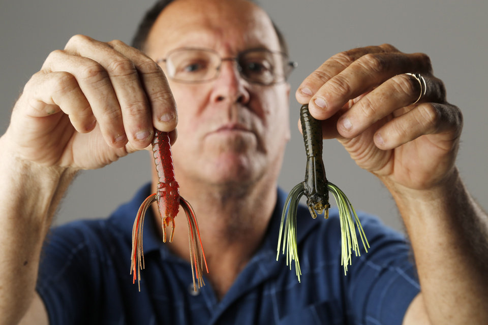 Greg Dorris holds two of his patented bass baits, called Whiskers. Photo by Doug Hoke, The Oklahoman DOUG HOKE - THE OKLAHOMAN
