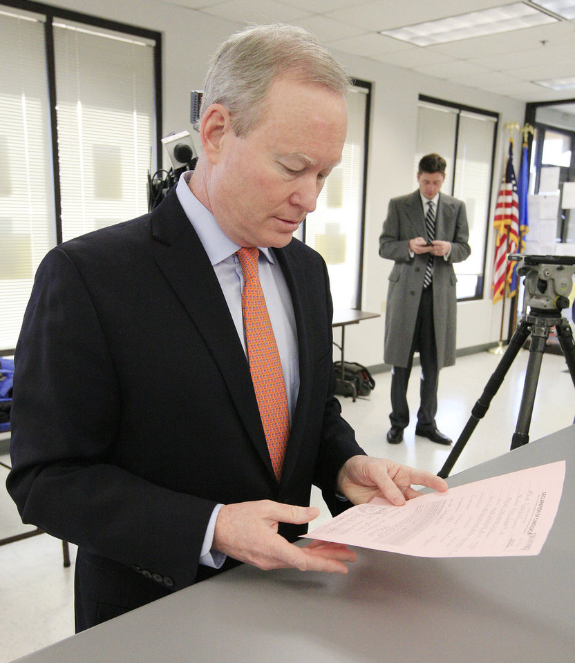 Photo - Oklahoma City Mayor Mick Cornett looks at his paperwork while filing for re-election at the Oklahoma County Election Board in Oklahoma City Wednesday, Jan. 29, 2014.  Photo by Paul B. Southerland, The Oklahoman