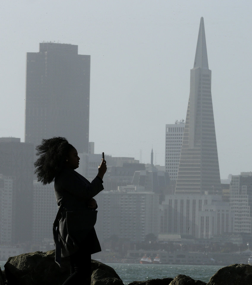 Photo - A woman photographs the San Francisco skyline Thursday, Dec. 10, 2015, as seen from Treasure Island in San Francisco Bay. Another storm system is expected this afternoon, bringing rain to the Bay Area. (AP Photo/Ben Margot)