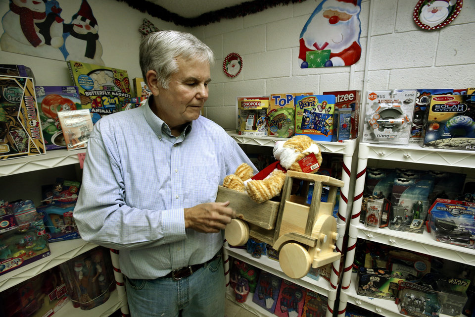 Cleveland County Christmas Store co-Chairman Brad Hawkins holds a handmade wooden truck and a stuffed toy that were among donations delivered to the store Tuesday by University of Oklahoma employees.  PHOTO BY STEVE SISNEY, THE OKLAHOMAN