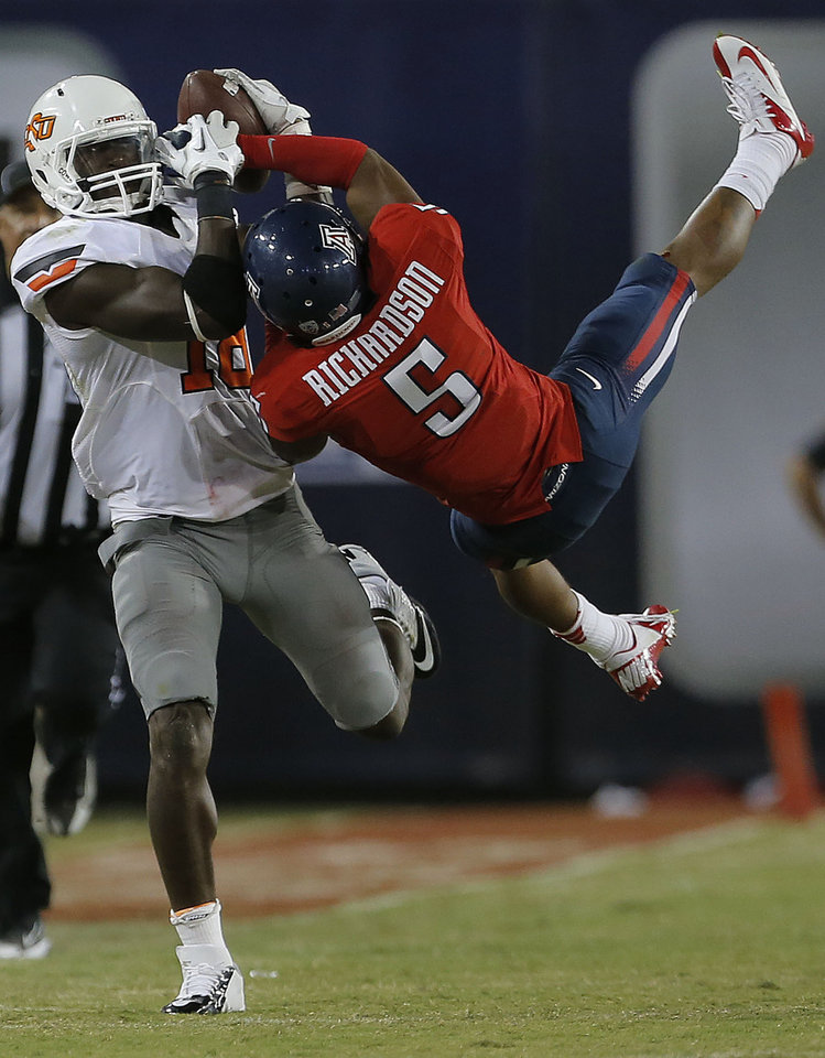 Photo - Oklahoma State's Blake Jackson (18)  makes a catch as Arizona's Shaquille Richardson (5) defends during the college football game between the University  of Arizona and Oklahoma State University at Arizona Stadium in Tucson, Ariz.,  Sunday, Sept. 9, 2012. Photo by Sarah Phipps, The Oklahoman