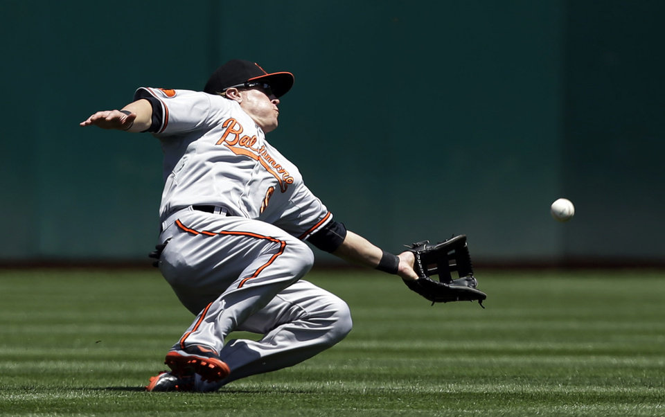 Photo - Baltimore Orioles left fielder Nate McLouth makes a sliding attempt at a pop fly from Oakland Athletics' Brandon Moss during the second inning of a baseball game, Sunday, April 28, 2013, in Oakland. Calif. Moss got a single on the play. (AP Photo/Marcio Jose Sanchez)