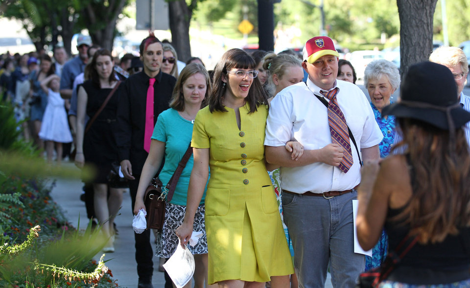 Photo - Kate Kelly, center, walks with supporters to the Church Office Building of the Church of Jesus Christ of Latter-day Saints during a vigil Sunday, June 22, 2014, in Salt Lake City. While Kate Kelly's former church leaders meet in Virginia on Sunday night to decide if she'll be ousted from her church, the founder of a prominent Mormon women's group will hold a vigil in Salt Lake City along with hundreds of her supporters. The leader of Ordain Women is accused of apostasy, defined as repeated and public advocacy of positions that oppose church teachings. (AP Photo/Rick Bowmer)