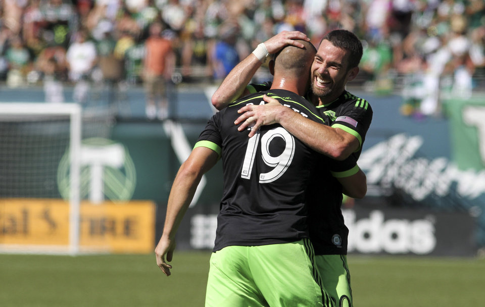 Photo - Seattle Sounders player Zach Scott, right, congratulates teammate Chad Barrett on scoring a goal against the Portland Timbers during an MLS soccer game in Portland, Ore., Sunday, Aug. 24, 2014. (AP Photo/Natalie Behring)