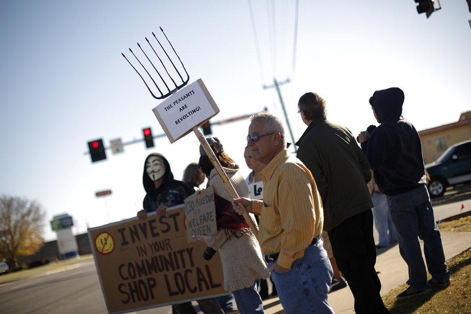 Johnny Mansfield stands with a pitchfork and sign during an Occupy OKC demonstration at a Wal-Mart in Del City, Friday, Nov. 23, 2012.  Members of the Occupy movement were protesting for Wal-Mart worker's rights to a living wage. Photo by Garett Fisbeck, The Oklahoman