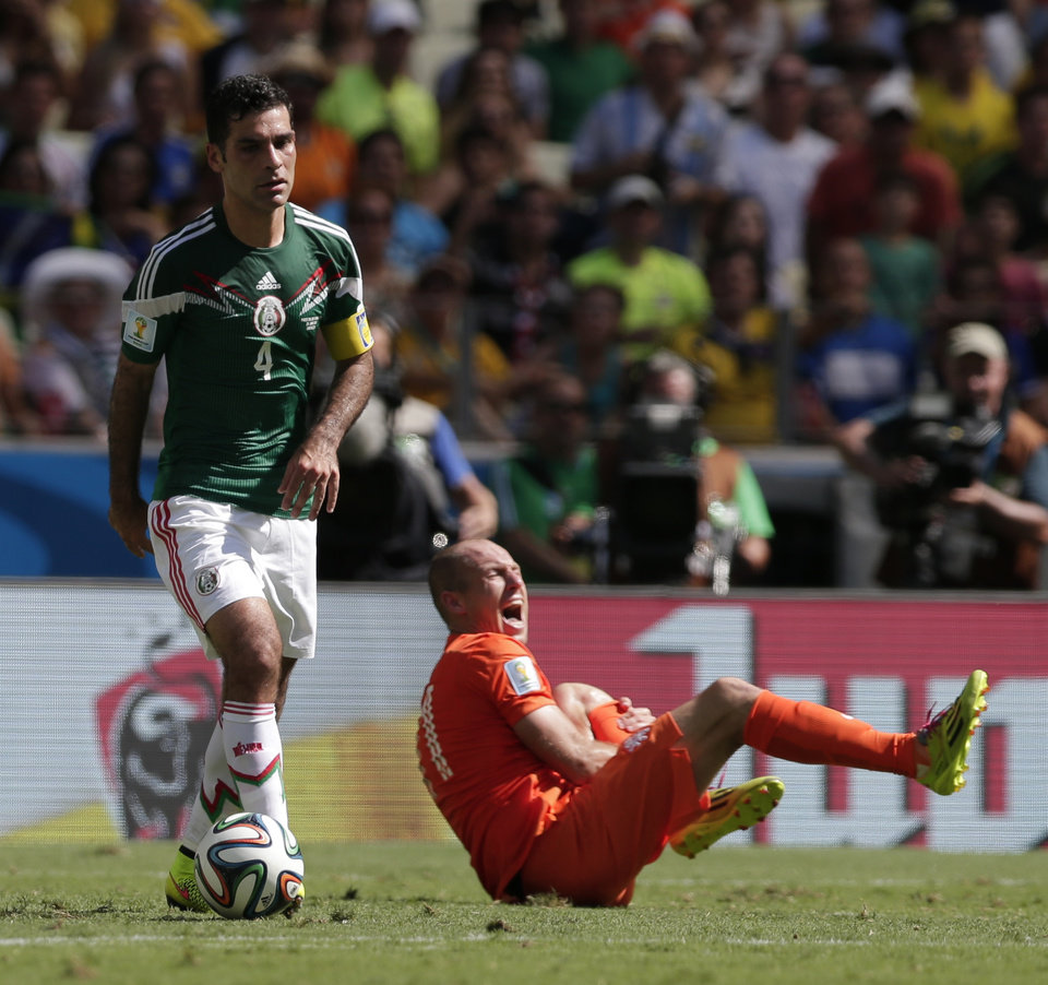 Photo - Mexico's Rafael Marquez controls the ball as Netherlands' Arjen Robben, right, grimaces during the World Cup round of 16 soccer match between the Netherlands and Mexico at the Arena Castelao in Fortaleza, Brazil, Sunday, June 29, 2014. (AP Photo/Marcio Jose Sanchez)