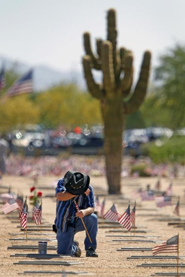 Jack Warren becomes emotional as he kneels at the grave of his father, Billy Warren, on Memorial Day at the National Memorial Cemetery of Arizona, Monday, May 30, 2011, in Phoenix. (AP Photo/The Arizona Republic, David Kadlubowski) MARICOPA COUNTY OUT; MAGS OUT; NO SALES  ORG XMIT: AZPHP101
